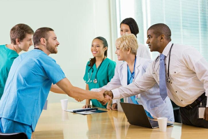 Hospital staff interviewing potential employees in board room